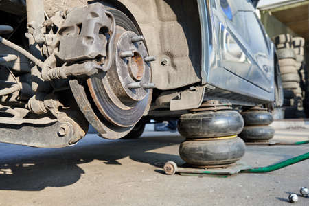 Photo for Car without wheels lifted up with jacks during wheel replacement. Seasonal change of car tires. - Royalty Free Image