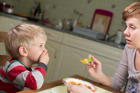 Foto de Blond Boy Holds Hand on his Mouth to Stop Eating - Imagen libre de derechos