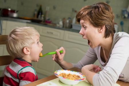Photo pour Little boy eating his dinner - image libre de droit