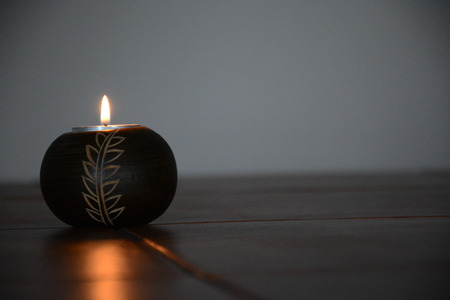 A candle burns in a darkened room.