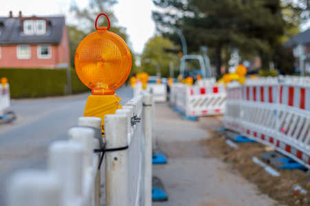 Photo pour red and white barricades with warning lights at a street in the residential zone, depth of field - image libre de droit