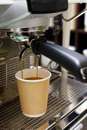 Photo pour Closeup of espresso pouring from coffee machine in cardboard cup for take away. Shallow focus. - image libre de droit