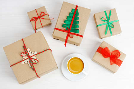 Foto für Group of gift boxes wrapped in kraft paper, tied with twine and decorated with a ribbons on white wooden table. - Lizenzfreies Bild