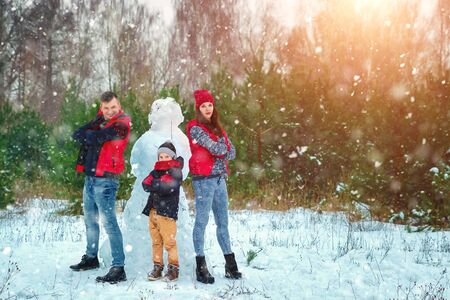 Happy family in warm clothes in the winter outdoors. Concept of holidays, holidays, winter, new year, day of grace. Family relationships, happy marriage.