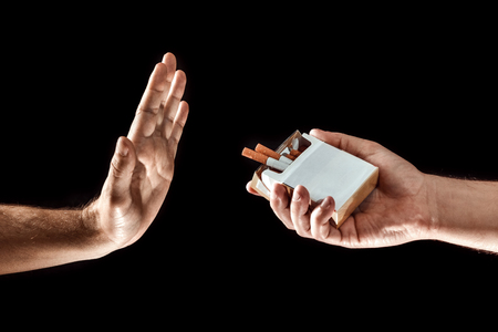 Foto de Hands close-up, stop smoking gesture, give up cigarettes, stop smoking. Creative background. The concept of smoking kills nicotine poisons. - Imagen libre de derechos