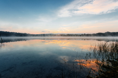Photo pour Beautiful, red dawn on the lake. The rays of the sun through the fog. The blue sky over the lake, the morning comes, the forest is reflected in the water. - image libre de droit