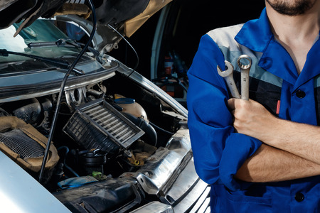 Photo for Male's hands close-up with wrenches. The auto mechanic works in the garage. Repair service. Maintenance of the car, car repair. - Royalty Free Image