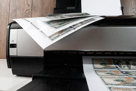 Photo pour Printer and printed US dollars, counterfeit banknotes, currency counterfeiting. Counterfeiters, printing press, inflation. - image libre de droit