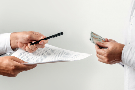Photo pour Hands, money, offers to sign a contract for a bribe, isolated on a white background. One hundred dollar bills. The concept against corruption in business activities, against bribery. - image libre de droit