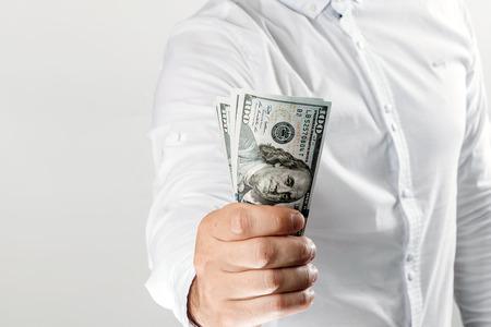 Photo pour Money in the hands of a businessman, US dollars. The concept of corruption, pledge, bribery, fraud, auction bidding - image libre de droit