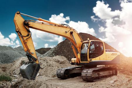 Photo pour Excavator at the construction site, sand, crushed stone, against the blue sky background. Construction equipment, construction. - image libre de droit
