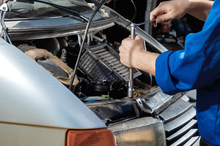 Photo pour Male's hands close-up with wrenches. The auto mechanic works in the garage. Repair service. Maintenance of the car, car repair. - image libre de droit