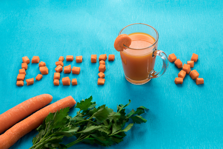 Foto für Inscription detox, top view, carrot juice in a glass on a blue background. - Lizenzfreies Bild