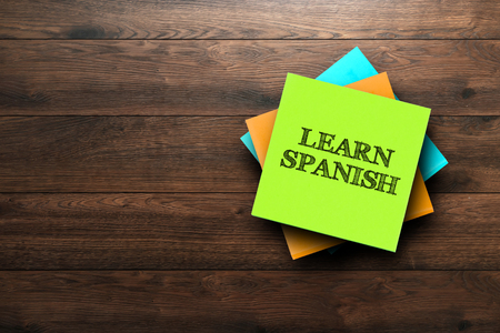 Photo pour Learn Spanish, the phrase is written on multi-colored stickers, on a brown wooden background. Business concept, strategy, plan, planning. - image libre de droit