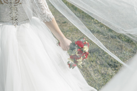 Foto de Close up of a bride holding a wedding bouquet with red and white roses. - Imagen libre de derechos