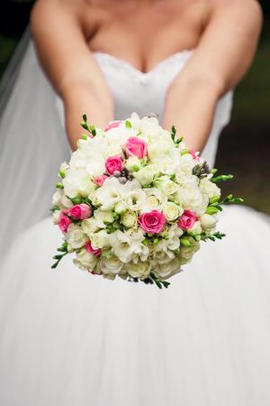 Photo pour The bride is holding a wedding bouquet in her hands in nature - image libre de droit