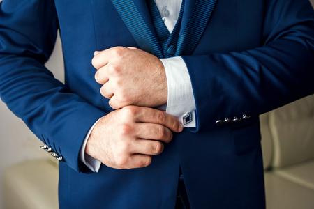 Foto de A man in a blue suit straightens his sleeves - Imagen libre de derechos