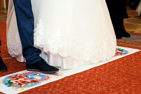 Foto de Newlyweds stand on the red wedding towel - Imagen libre de derechos
