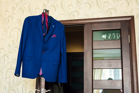 Photo for Jacket, tie and shirt hanging blue jacket, brown door, yellow walls - Royalty Free Image