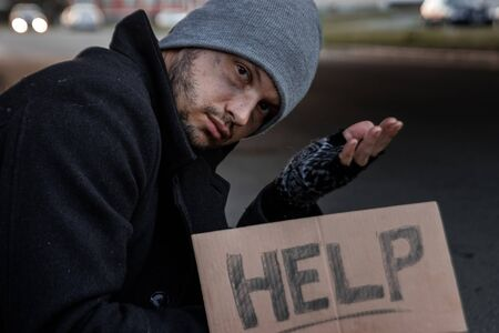 Photo for A man, homeless, a person asks for alms on the street with a Help sign. Concept of homeless person, addict, poverty, despair - Royalty Free Image
