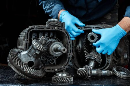 Photo pour Hands of a male repairman in blue gloves on a background of a gearbox, close-up. Repair box predach, repair of used cars. Metal background. - image libre de droit