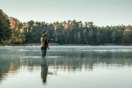 Photo pour A male fisherman on the lake is standing in the water and fishing for a fishing rod. - image libre de droit