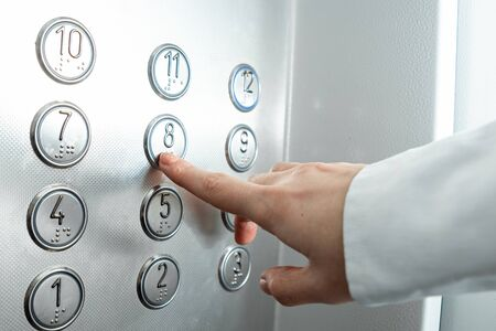 Foto de Female hand, finger presses the elevator button. up the career ladder - Imagen libre de derechos