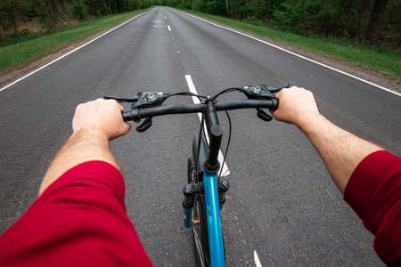 Foto de Male hands on the handlebars of a bicycle riding on a road in the forest. The concept of a healthy lifestyle, cardio training. Copyspace - Imagen libre de derechos