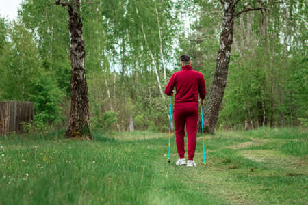 Foto per A man in a tracksuit is engaged in Nordic walking. The concept of a healthy lifestyle, cardio training. Copyspace - Immagine Royalty Free