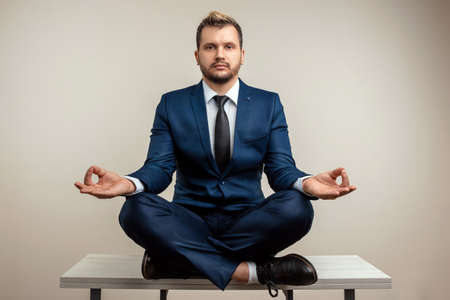 Photo for A businessman in a blue suit at a work table. Meditation at work. Emotional work. Multitasking, effective business worker concept - Royalty Free Image