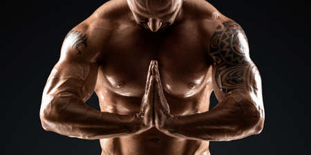 Photo pour Male bodybuilder with light stubble and bare torso shows muscularity against a dark background. The concept of a fitness club, doing sports, weightlifting. Copy space - image libre de droit