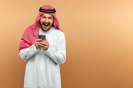 Photo pour Arab man businessman in national clothes shouts displeased into the receiver of a smartphone. Middle east business concept, good idea, investment, anger - image libre de droit
