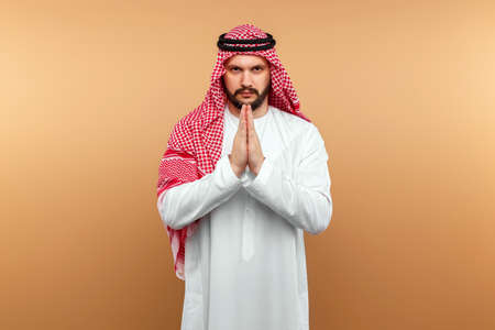 Photo pour Arab man businessman in national clothes folded his hands in prayer, like, beige background. Dishdasha, kandora, thobe, middle east traditional menswear concept, islam. Copy space - image libre de droit