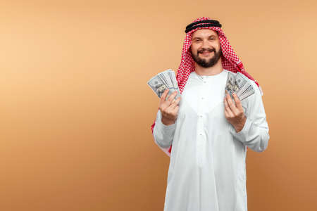 Photo pour Arab man businessman in national clothes rejoices in dollars in his hands, great profit. Business concept in the middle east, oil sale, investment - image libre de droit