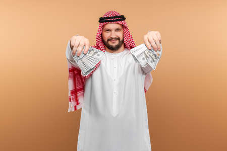 Photo pour Arab man businessman in national clothes is holding dollars in his hands. Business concept in the middle east, oil sale, investment - image libre de droit