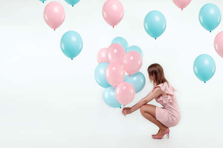 Photo pour A beautiful young girl sits with blue and pink balloons on a white background. Happiness, spring, holiday - image libre de droit