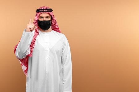 Photo pour An Arab man in national clothes wearing a medical mask. Dishdasha, kandora, thobe, Islam,  Protection against contagious disease. Copy space - image libre de droit
