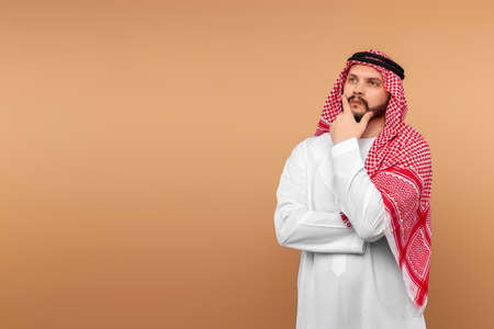 Photo pour The Saudi Arab man is thinking about something. Dishdasha, kandora, thobe, islam. Copy space - image libre de droit