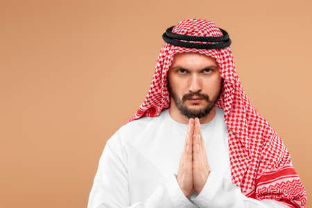 Photo pour An Arab man in national dress is praying on a beige background. Dishdasha, kandora, thobe ,, traditional men's clothing of the Middle East, islam, faith. Copy space - image libre de droit
