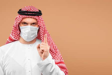Photo pour An Arab man in national clothes wearing a medical mask. - image libre de droit