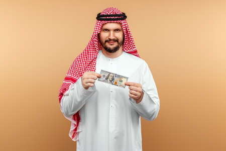 Photo pour An Arab man in a national costume holds dollars in his hands on a beige background - image libre de droit