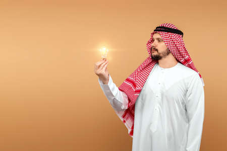 Photo pour A man Arab holds a national costume holding a light bulb in his hand on a beige background. Concept idea, thought - image libre de droit