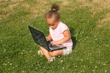 Excited Young Girl Conducting Business on Laptop while she is sitting down on the grass and clovers in the park. There is a beautiful reflection captured in the glossy black lid of the computer.