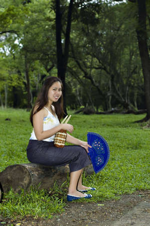 Part of series. Asian Woman sitting on a log bench  while showing off her blue chinese wooden fan . There are woods at the background.