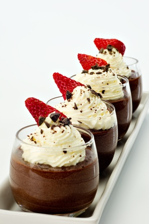 Photo for Chocolate Mousse for four topped with whipped cream, dark chocolate shavings and a strawberry. - Royalty Free Image