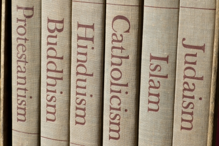Book spines listing major world religions - Judaism, Islam, Catholicism, Hinduism, Buddhism and Protestantism.