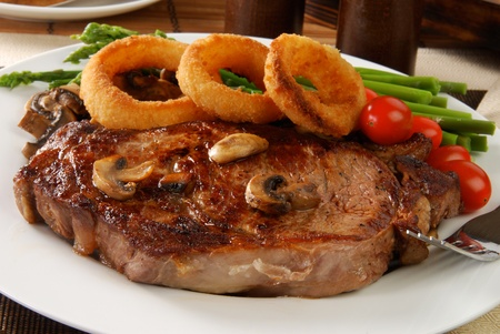 A grilled rib steak topped with onion rings