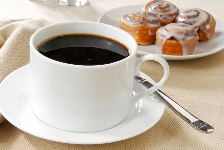 A cup of black coffee and cinnamon rolls for breakfast