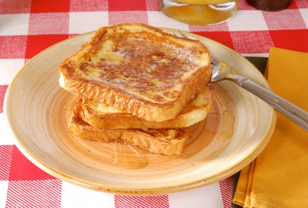 A plate of golden brown french toast with syrup