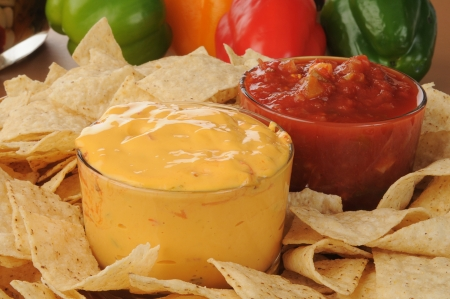 Close up of a tray of tortilla chips with salsa and cheese dip